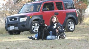 Dr. Beagan sitting in front of car with two dogs